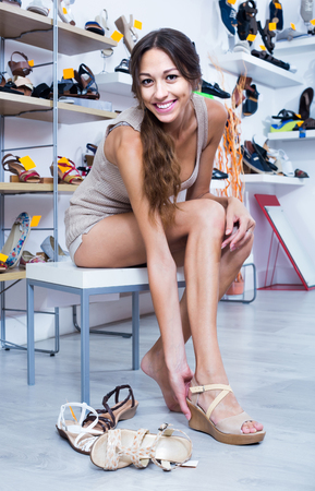 happy russian girl customer trying on chosen shoes in footwear department Stock Photo