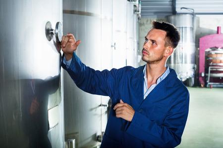 diligente: hombre joven diligente eficiente en la capa que toman notas en la sección de fermentación secundaria en fábrica de vino