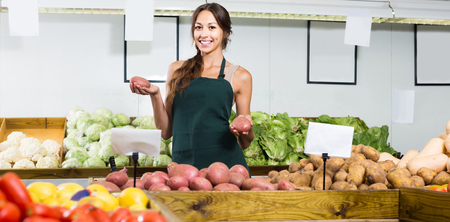 food shop: portrait of young positive european woman in apron selling organic potatoes in shop