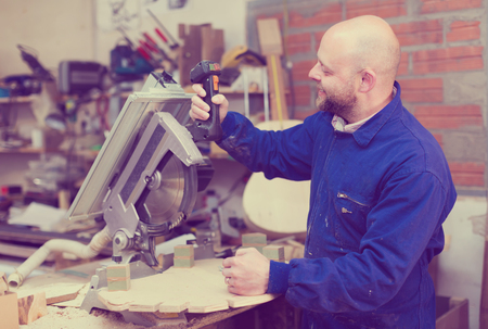 atelier: Positive skilled atelier working on a machine at guitar workshop Stock Photo
