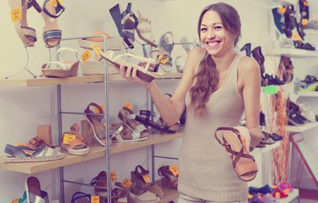 comprando zapatos: sonriente joven cliente femenina eligiendo entre dos pares de zapatos y comprar en la tienda Foto de archivo