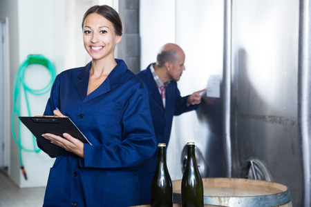 wine register: Portrait of woman standing with cardboard in hands in fermentation compartment on factory Stock Photo