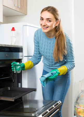 householder: Positive young maid doing oven clean-up in domestic kitchen