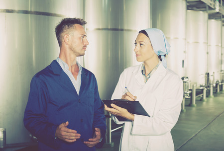fermentation: Two young beverage industry employees in protective uniform and taking notes in secondary fermentation section