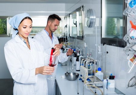 attentive: attentive young man and woman experts checking wine quality in wine manufactory laboratory