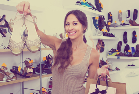 chosen: happy young woman customer with shopping bags holding chosen pair of shoes in fashion store