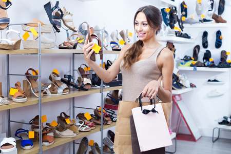 chosen: Glad young woman customer with shopping bags holding chosen pair of shoes in fashion store