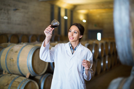 Young cheerful woman wearing coat holding glass of wine in large cellar on winery factory