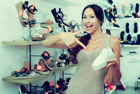 desired: Attractive young female customer showing desired shoe in boutique