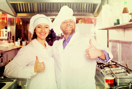 house robes: adult cooks cooking at professional kitchen in the take-away  restaurant