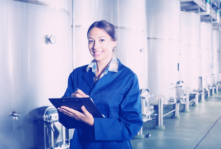 wine register: Smiling woman winery employee in uniform taking off data from equipment in winery fermentation section