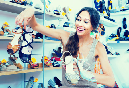 chosen: positive young woman 30s standing in boutique with many chosen shoes in hands