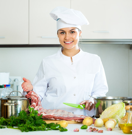 Positive female chef working with pork ribs in kitchen