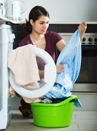 unwashed: Unhappy brunette girl with dirty curtains near washing machine