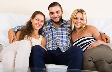 bisexual women: Smiling modern polygamous family with one husband and two wives Stock Photo