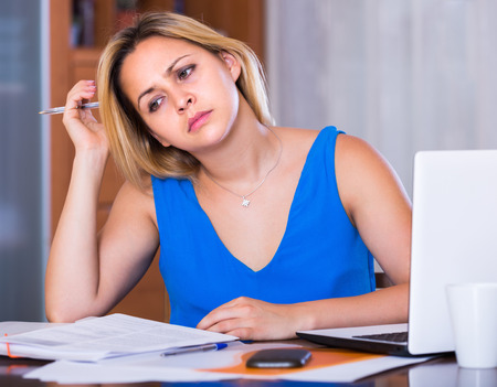 yuppie: Exhausted young blonde woman making mistakes in her work Stock Photo