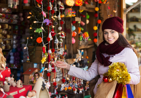 overspending: Portrait of young positive woman shopping at festive fair before Xmas Stock Photo