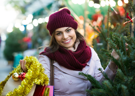 overspending: Portrait of happy charming young brunette choosing New Years tree in fair