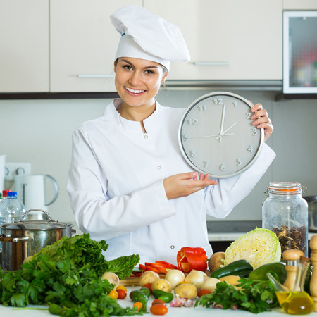 Smiling young woman in uniform cooking vegetables and looking at clock at kitchen