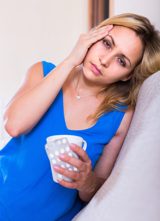splitting headache: Portrait of young blonde woman suffering from headache at home Stock Photo