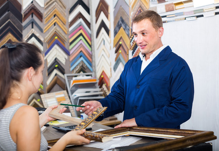 portrait of happy russian man seller taking order on picture frame from customer at counter in store