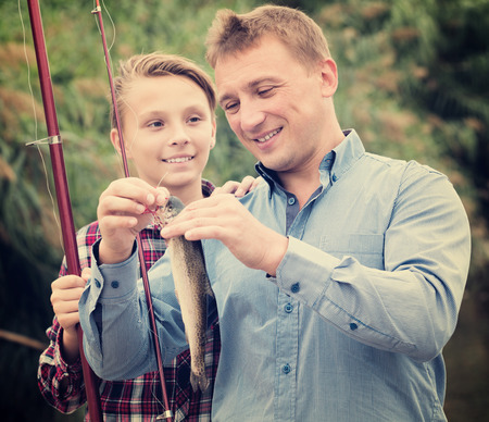 gudgeon: Cheerful man with teenager boy releasing fish from hook outdoors. Focus on the man