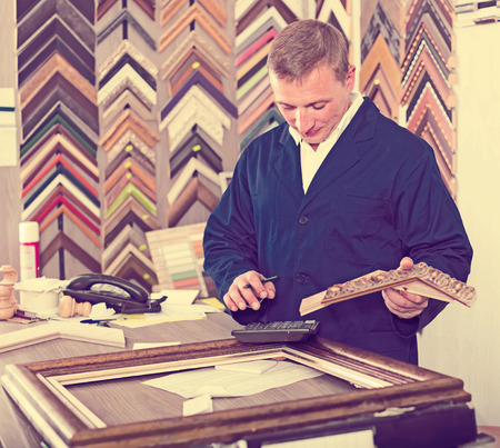 picture framing: male seller standing in picture framing studio with wooden details