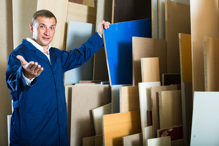 picture framing: portrait of man in uniform choosing compressed densified wood in picture framing atelier Stock Photo