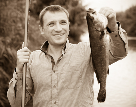 Glad man holding a fish after fishing on river side