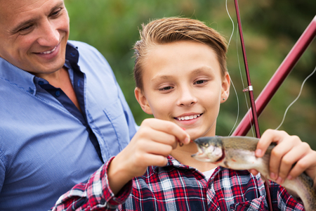 Happy teenage boy and his father holding taken freshwater fish in hands
