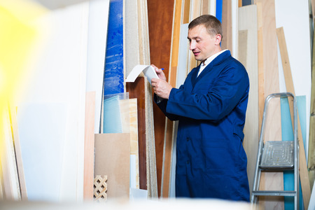 picture framing: portrait of positive american man in uniform choosing compressed densified wood in picture framing atelier