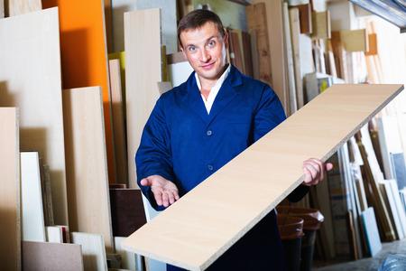 diligente: La sonrisa del hombre diligente vistiendo ropa protectora de pie con la madera contrachapada en la tienda Foto de archivo