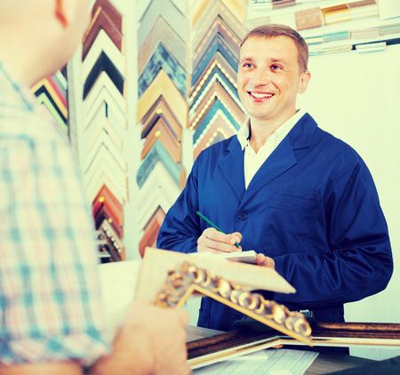picture framing: ?cheerful  man seller talking to customer in picture framing studio