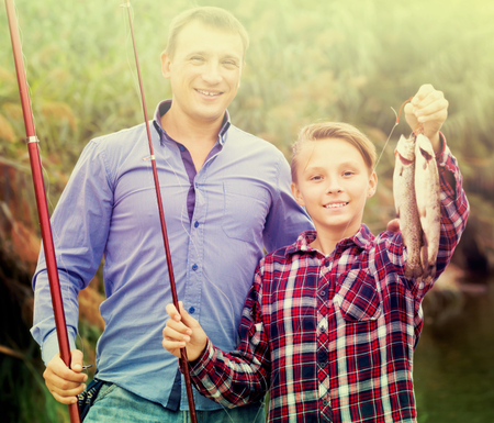 Portrait of glad father with teenager son looking at fish on hook in hands outdoors Stock Photo