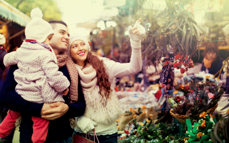 5s: Smiling parents and little child buying red Euphorbia at Christmas fair. Focus on woman Stock Photo