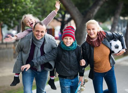2 november: Cheerful active family with two smiling children spending weekend together outdoors Stock Photo