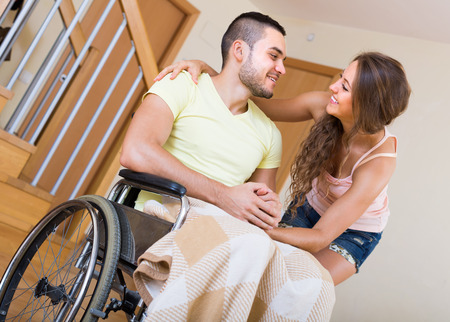 invalidity: Romantic relationships between young girl and smiling man in invalid chair