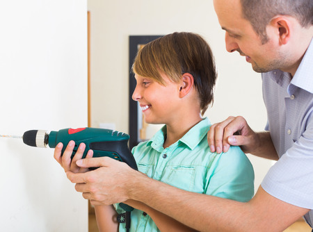 modifying: Positive son helping proud father to drill wall at home