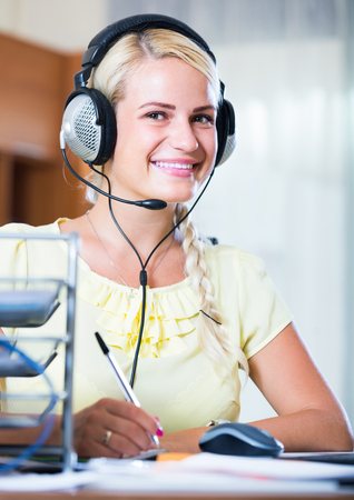 young american  girl answering the call of technical support and smiling