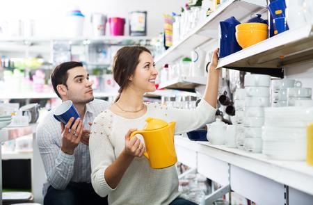 utensilios de cocina: Positive man and woman buying ceramic tableware in shop cookware