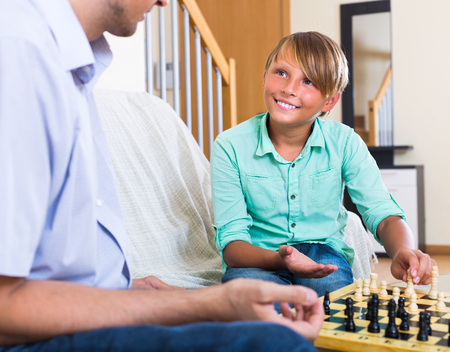 Smiling dad and son playing chess together at home Stock Photo