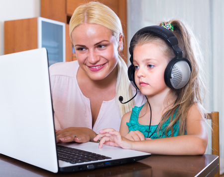 Young smiling blonde woman and her little daughter chatting with relatives online Stock Photo
