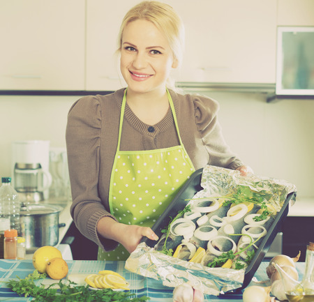 fryingpan: Happy smiling blonde woman cooking fish with lemon in kitchen at home Stock Photo