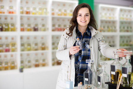 eau de perfume: Portrait of positive american brunette shopping in perfume store Stock Photo