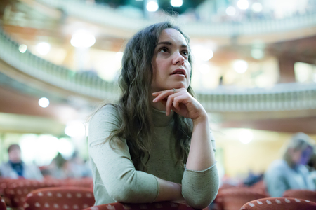 playhouse: portrait of amazed woman sitting in theatre salon and watching show