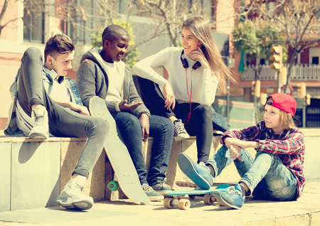 blabbing: Happy teens spending time together and talking in sunny day