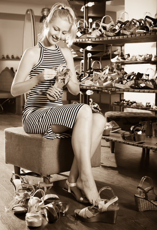 Young glad girl trying on chosen shoes in footwear department Stock Photo