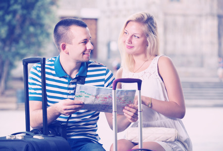 Young cheerful traveling couple searching for direction using paper map in town