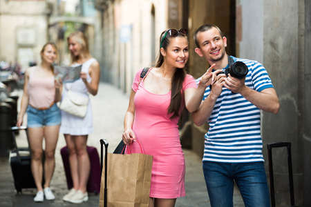 cheerful young tourist couple looking satisfied after shopping holding paper bag and camera outdoors