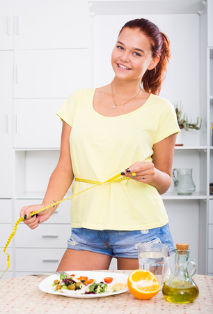 smiling young teenager girl having measuring tape around her waist on kitchen